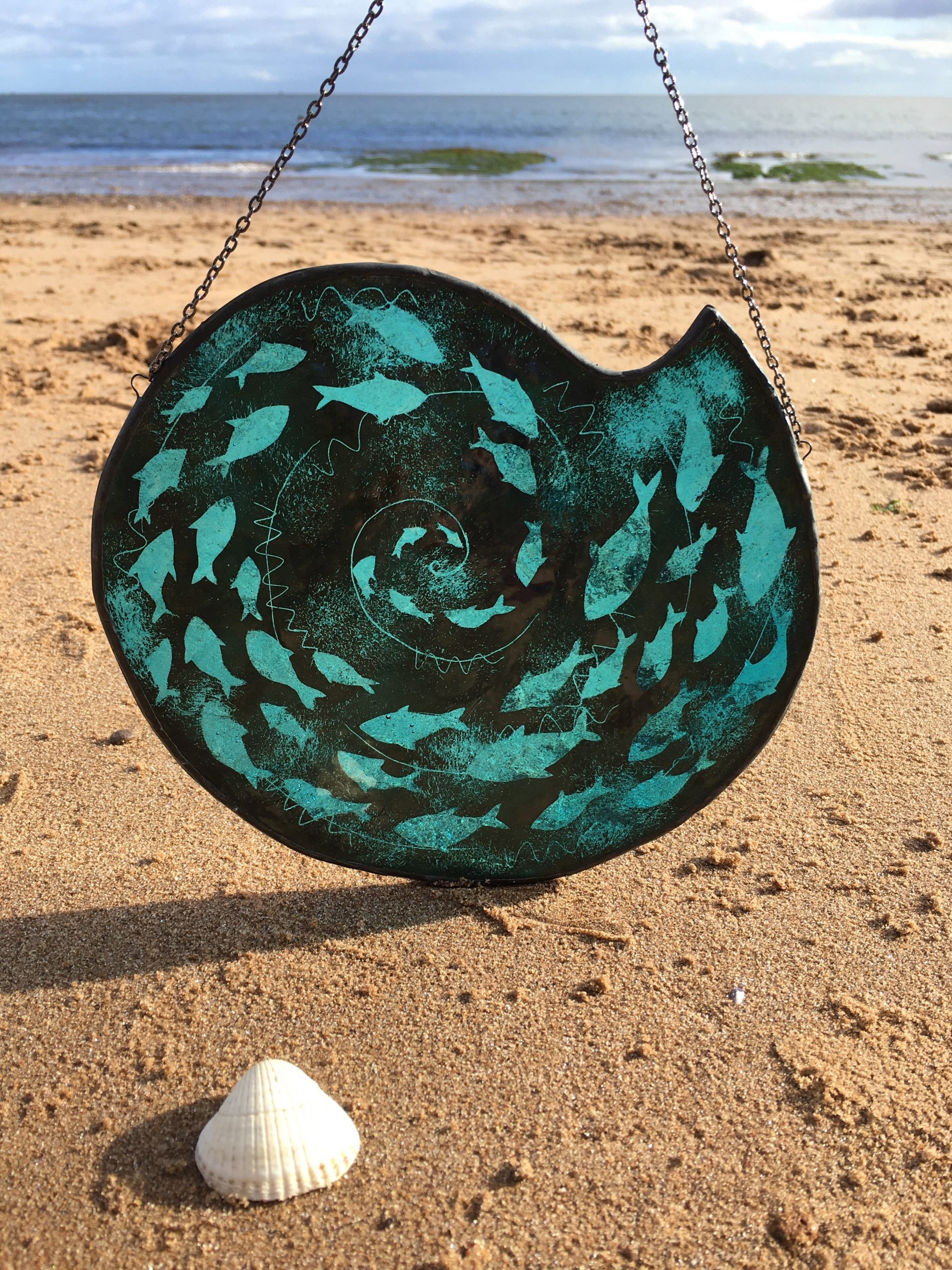 Stained glass fish spiral on beach