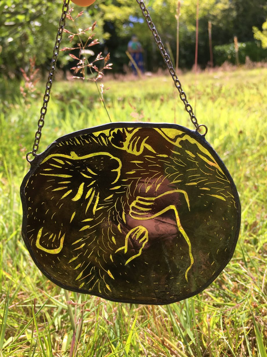 Stained glass sleeping field mouse sun catcher in field