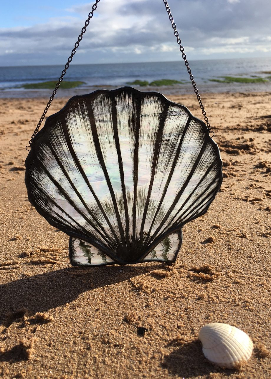 Stained glass scallop on beach