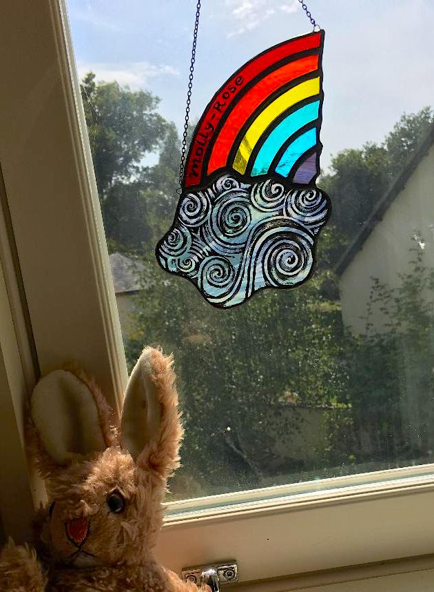 Stained glass sun catcher of rainbow and cloud on window