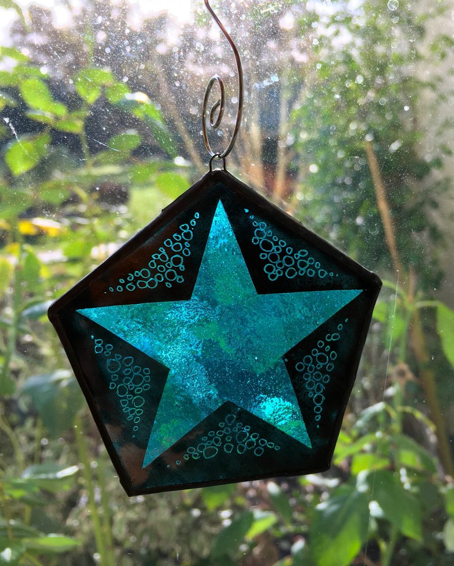 Blue stained glass xmas star in window