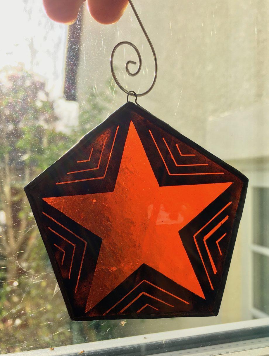 Orange stained glass Xmas star in window