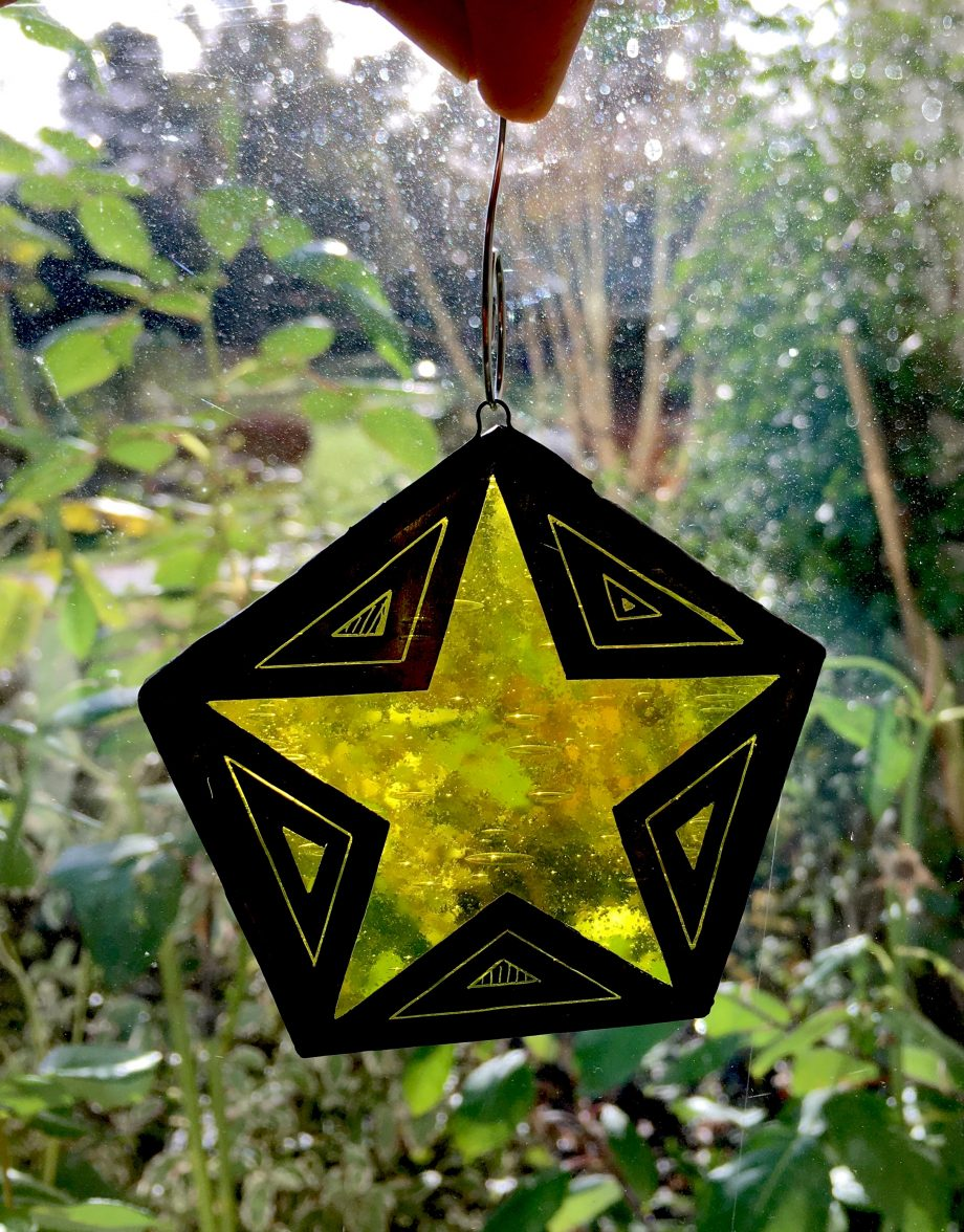 Yellow stained glass xmas star in window